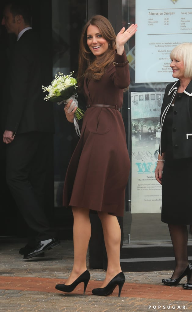 """Kate Middleton wrapped up her baby bump in a brown Hobbs coat today when she arrived at the National Fishing Heritage Center in Grimsby, England. She clutched a gift of white flowers as she waved at the gathered crowd and walked into the Center in black L.K. Bennett pumps. Kate shared that the baby is """"very much so"""" kicking when asked by a fan whether she'd felt movement yet. There is also new speculation that Kate and Prince William are expecting a girl after Kate stopped herself from saying """"my daughter"""" during today's appearance.  It's been a busy few days for Kate, who  traveled to the Swiss Alps this weekend with Prince William and Prince Harry to attend a friend's wedding and get in a bit of fun on the slopes. Despite her snowy vacation, Kate hasn't been shying away from her royal duties and was last seen making an appearance at Hope House, a rehab center for women, in London. She may have a full schedule of work ahead of her until the Summer — Kate's due in July."""