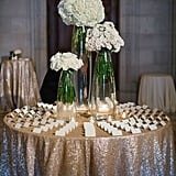 Guide guests to the place card table with an asymmetrical floral arrangement and glittery tablecloth.