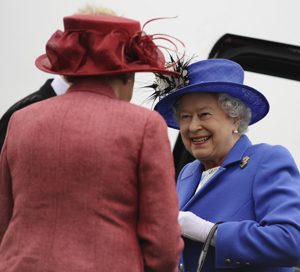 The queen smiled at the racegoers.