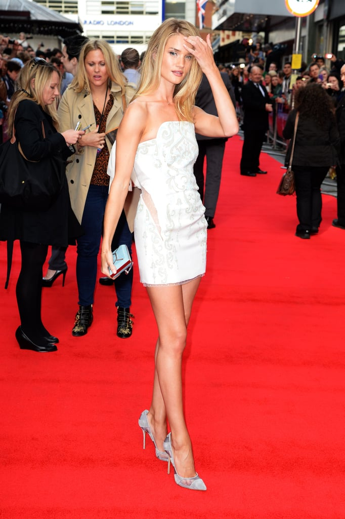 Rosie looks radiant on the red carpet in a mini dress with a cutout back and matching silver shoes and clutch-bag.