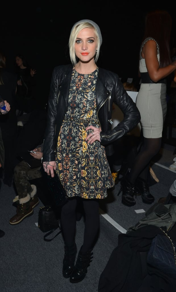 Ashlee Simpson roughed up her printed dress with a quilted leather jacket and gray beanie while sitting front row at Nicole Miller during NYFW.
