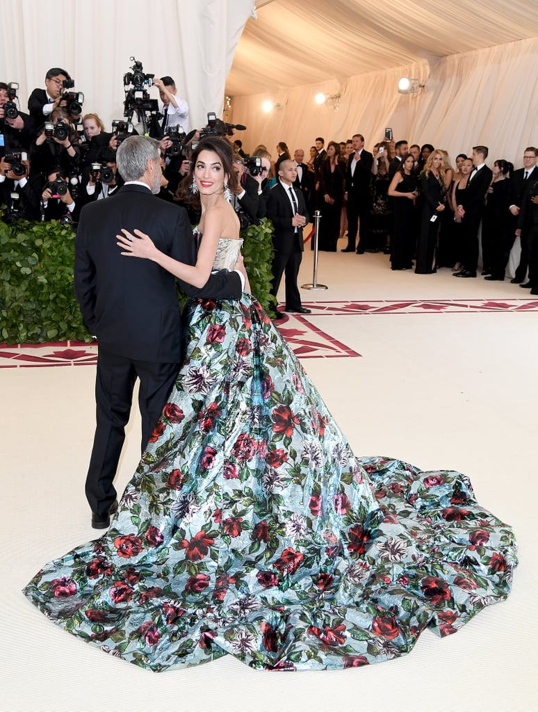Amal and George Clooney enjoyed a fun night out as they attended the Met Gala on Monday in NYC. The couple, who are parents to twins Ella and Alexander, made one stylish pair as they walked the red carpet together outside of The Metropolitan Museum of Art in NYC. While George wore a black suit and bow-tie, Amal, who is a cohost for this year's event, stunned in a floral bustier and train over sleek navy blue pants.  The appearance comes at an exciting time for the parents of two. While George turned 57 last weekend, their son and daughter are getting ready to celebrate their very first birthday on June 6. Even though they have kept their little ones out of the spotlight, they have given us a peak at their family life by gushing about them during interviews. We can't wait to see even more of the gorgeous couple when they attend the royal wedding later this month.       Related:                                                                                                           37 Times George and Amal Clooney Looked Madly in Love