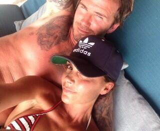 "Victoria shared a snap of herself lounging with husband David and wrote, ""Having a wonderful day with my family."" Source: Twitter user victoriabeckham"