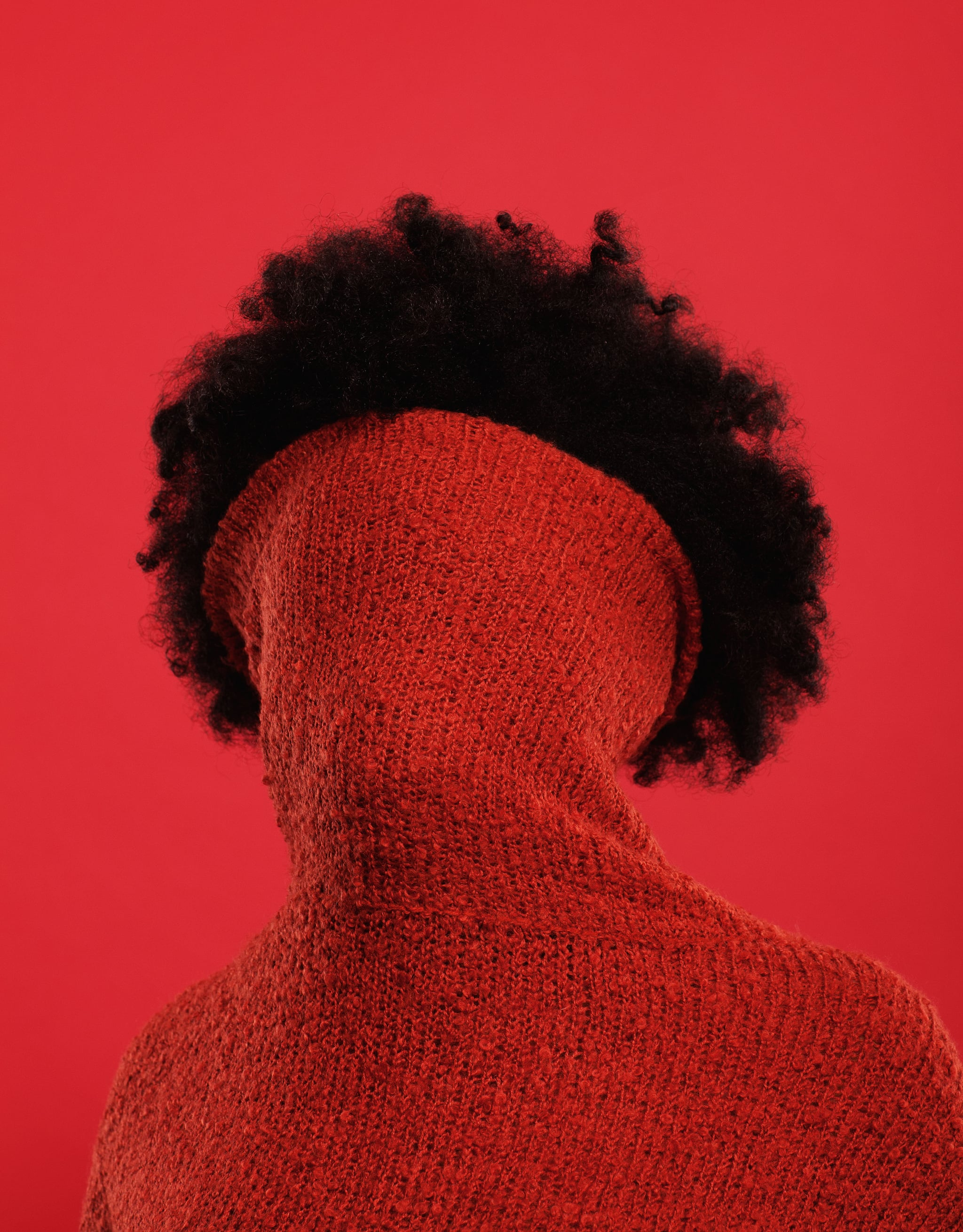 A woman with an afro hair style wearing a red jumper with turtle neck pulled up all the way to cover her face,  shot in front of a red background.