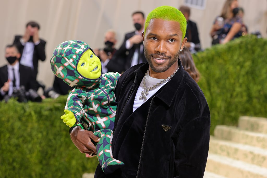 """Frank Ocean brought quite the interesting plus-one to the Met Gala. On Monday night, the singer appeared on the red carpet donning lime green hair, a Prada outfit, and a bizarre battery-operated baby in tow. That's right, Frank brought a robotic green baby to fashion's biggest night out, and it immediately had people talking. The green, freaky-looking arm candy had bright blue eyes, a full set of braces, and an applaudable ability to handle the paparazzi. Did we mention his name is Cody? Cody might appear to be right out of a home economics class to warn students of the repercussions of teen pregnancy, but he made it to the Met Gala in designer digs, so he's far too chic to be returned at the end of a semester. He happens to be wearing a custom onesie from Frank's new luxury brand Homer. During Frank's interview with Keke Palmer on the red carpet, he gushed over the host with his baby and said, """"He's starstruck, I'm starstruck,"""" and all was right in the world. Before spotting Frank at the US Open men's singles championships the day before, it had been a minute since we'd seen him out and about, and now, he's got a little brace face baby on his arm. So, we'll have to call him daddy. Check out photos of Frank and Cody at the 2021 Met Gala ahead, and prepare to be in awe over the cute red carpet duo.      Related:                                                                                                           Every Look From the 2021 Met Gala Red Carpet That We Can't Stop Talking About"""