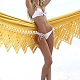 Candice Swanepoel posed against a yellow hammock.