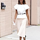 This is one of my favourite office chic looks for summer. I don't mind wearing a complete look of black in winter, although come summer, I want to wear whites and pastels and really embrace the season.  This is a perfect way to do this for work, without looking like you're going to a summer party. The skirt is long, sleek and fitted - yet still flowing enough to feel relaxed. The white shirt cinched at the waist, makes the look more office ready and yet the bold shoulders, cool belt and fun kitten heels, make it fashion forward whilst still very office appropriate. Also, note that her hair, whilst flowing and relaxed it perfectly polished - making this the ultimate summer work look.