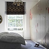 Hand-painted floral closet doors are whimsical and dream-like, and an ornate mirror and glitzy chandelier bring on the glam. Source