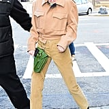 Kendall stepped out in neutral Winter Private Policy basics, including a camel-colored coat and trousers. She wore patent black booties and a green belt buckle bag, and a colorful graphic-print turtleneck stuck out from underneath.