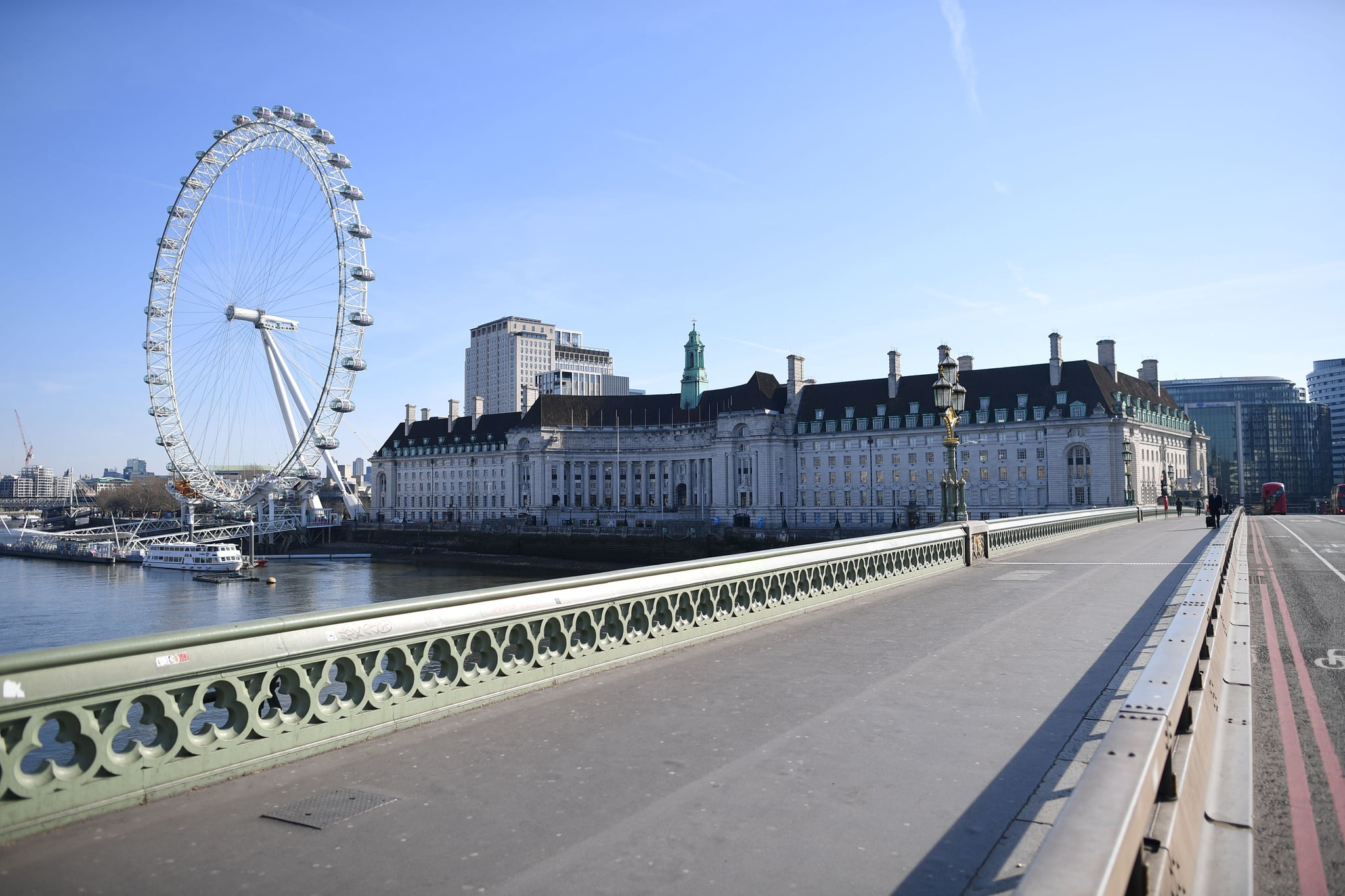 A picture shows a quiet Westminster Bridge with the London Eye in the background in central London in the morning on March 24, 2020 after Britain ordered a lockdown to slow the spread of the novel coronavirus. - Britain was under lockdown March 24, its population joining around 1.7 billion people around the globe ordered to stay indoors to curb the