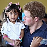 Prince Harry held 3-year-old Mayara Pereira in Brazil.