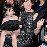 Milla Jovovich's daughter, Ever Anderson, held a fan as she watched the fashion show with her mom and her father, Paul W.S. Anderson.