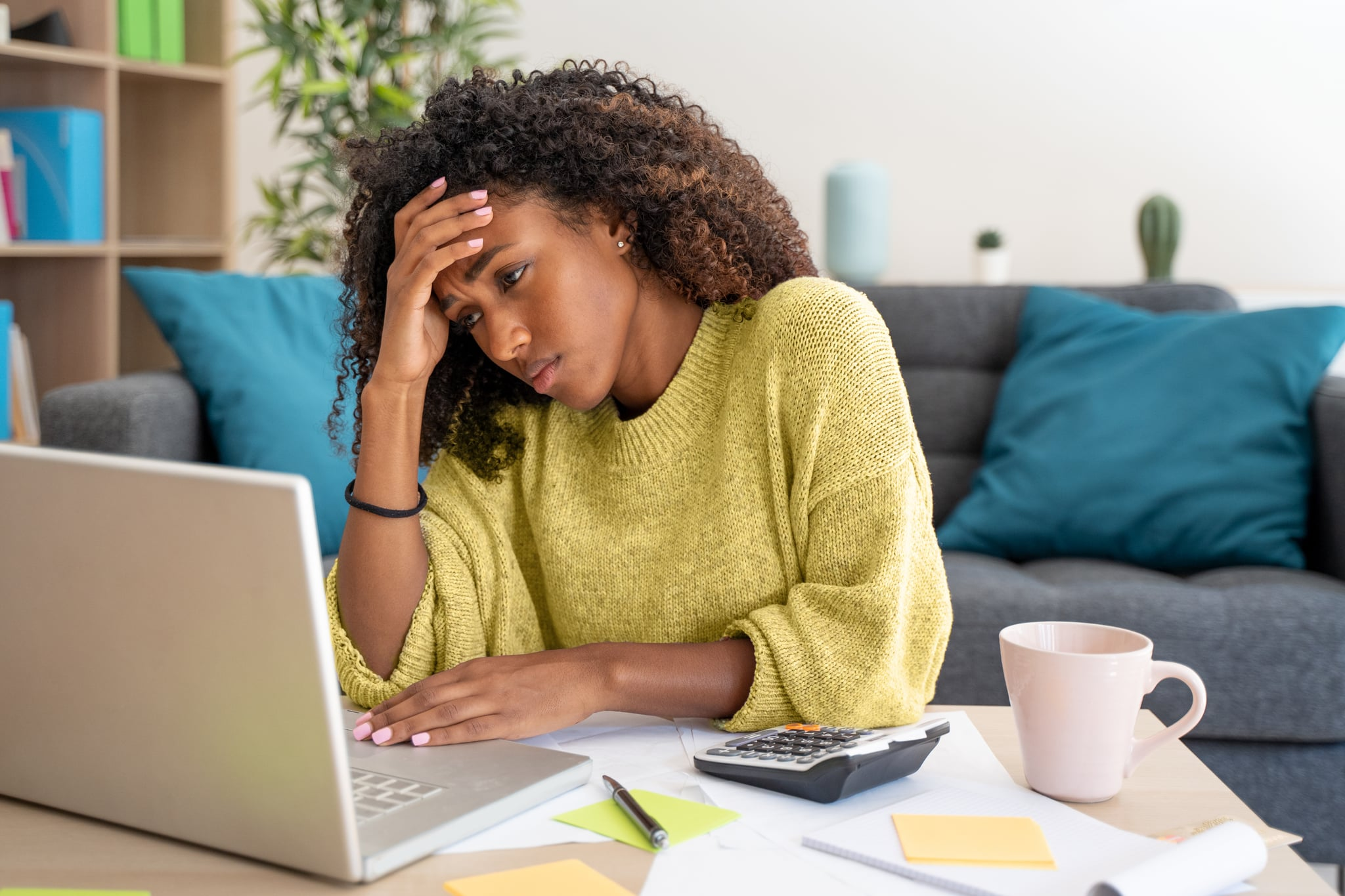Stressed black woman working at home alone