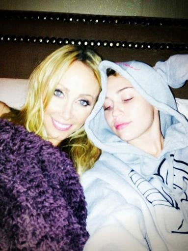 "Miley Cyrus snapped a photo while hanging in bed with her mom, Tish, with the caption ""Nothing a little mommy time can't fix."" Source: Twitter user MileyCyrus"