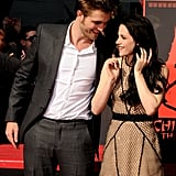 Robert Pattinson kept a close eye on Kristen Stewart as they got ready to leave their handprints in cement in 2011.