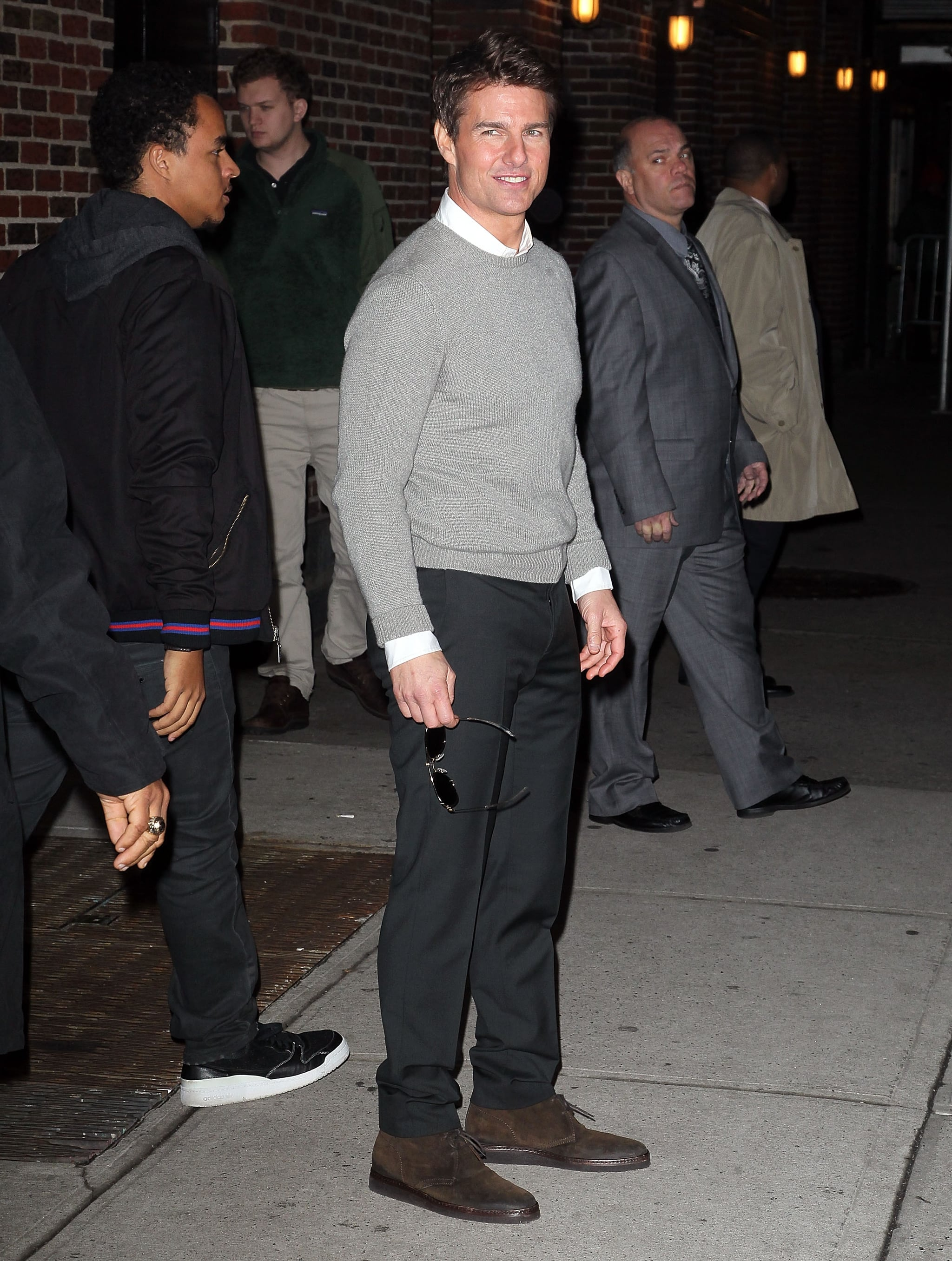 Tom Cruise wore a gray sweater and black pants.