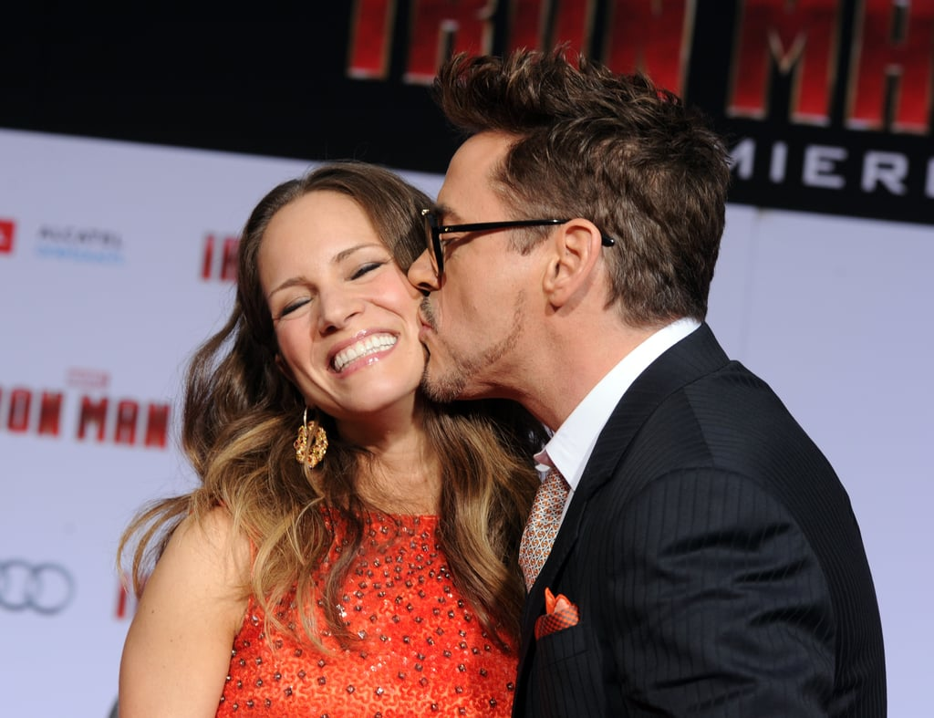 Robert Downey Jr. has been one of our biggest Hollywood crushes since the '80s, and his wife, producer Susan Levin, obviously agrees. The two first met on the set of Gothika in 2003, shortly after Robert split from his then-wife Deborah Falconer. Even though Susan turned down his advances twice, they eventually struck up a romance when he asked her out for a third time, and they continued dating after production wrapped. He proposed on the night before her 30th birthday, and they tied the knot in New York in August 2005.  Aside from being loving parents to son Exton and daughter Avri, Robert also credits his wife for helping him get sober after a long struggle with drug and alcohol addiction. Not only have they supported each other off screen, but they have also worked together on movies like Sherlock Holmes and Iron Man 2. They even have their own production house called Team Downey. Over the course of their relationship, the two have made tons of cute appearances together, but there is one thing Robert always does to show his love — he gives Susan a sweet kiss on the head. See some of their best PDA moments below.