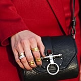 Stacked rings and a sleek mini messenger contrasted against a bright red jacket.