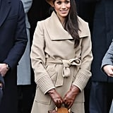 Wearing a Philip Treacy London embellished headpiece, camel Sentaler coat, Stuart Weitzman boots, Birks diamond snowflake earrings, and gloves and carrying a Chloé handbag.