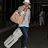 Cameron Diaz traveled with light colored luggage.