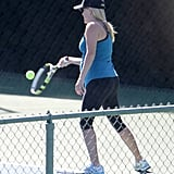 Reese Witherspoon wore black capri pants and a blue racerback tank top on the court.