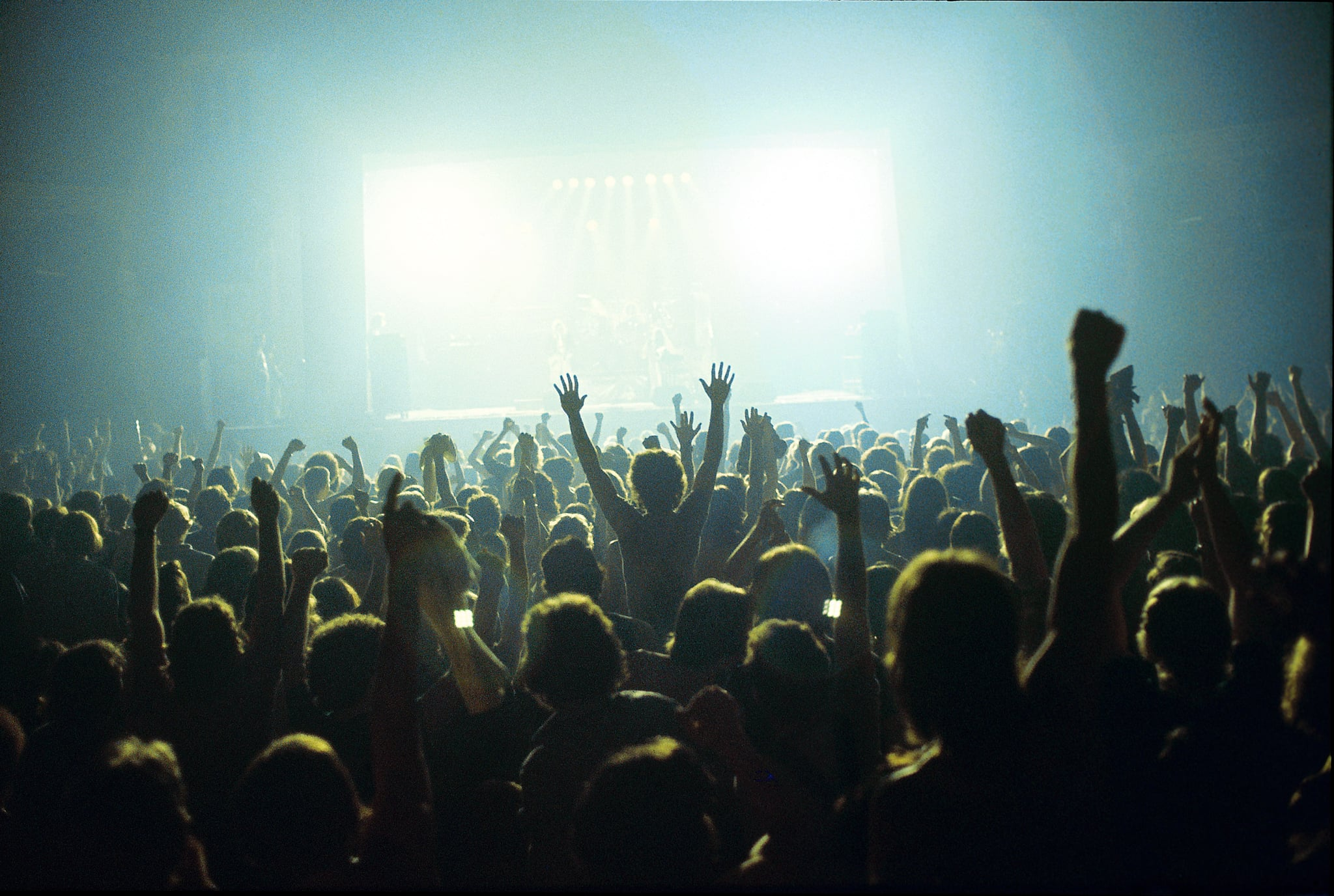 A general view of a rock concert taken from the back fo a venue showing the audience in silhouette raising their arms and cheering with bright lights shining from the stage, circa 1980. (Photo by Fin Costello/Redferns)