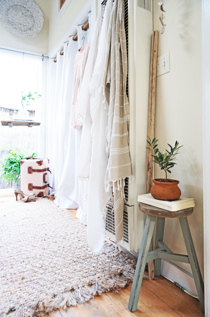 """Hanging tapestries and plants go a long way to conceal and enhance Whitney's home. """"Plants instantly make a space feel alive, fresh, and welcoming, and can transform a room of any size,"""" she explains. Plus, for the budget-conscious, she adds, """"Greenery is an easy way to regularly update the style of your home without hurting your wallet or the environment."""""""