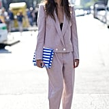 Making a case for matchy-matchy in blush suiting and a wide-brimmed hat.