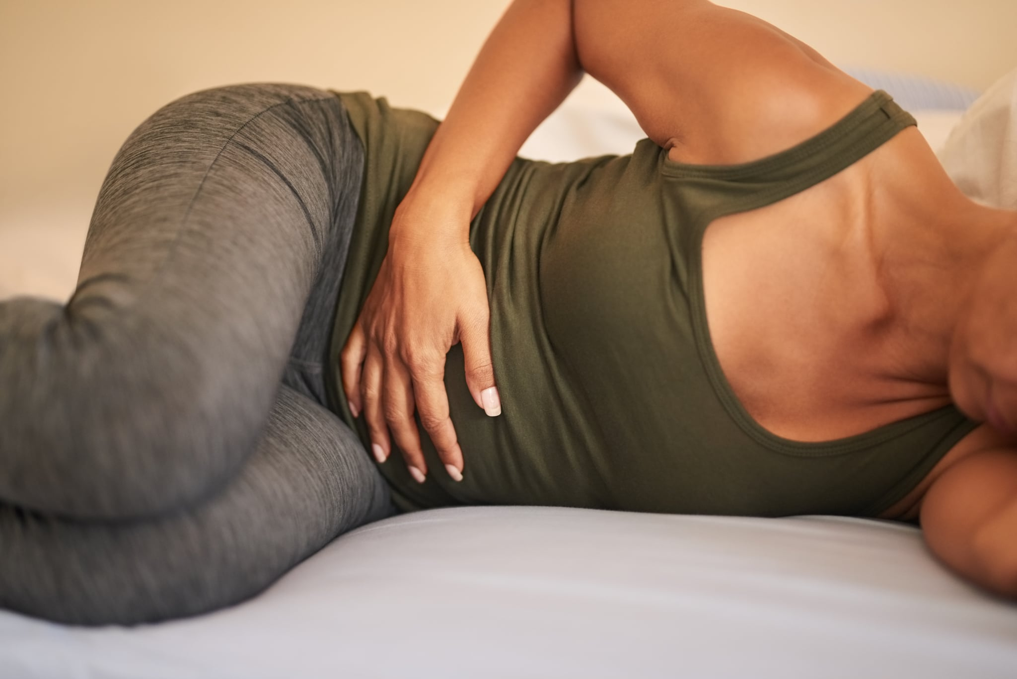 Shot of a woman suffering from stomach ache on bed