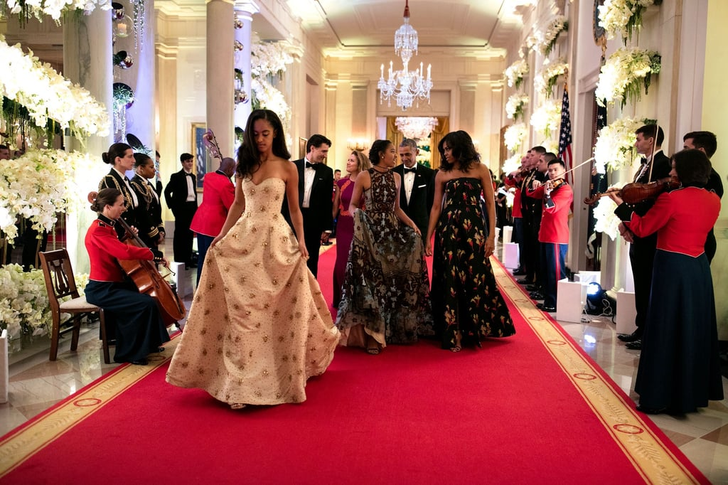 "Malia and Sasha Obama are blossoming into two beautiful young women! The daughters of Barack and Michelle Obama looked gorgeous on Thursday night when they attended their very first state dinner at the White House. The sisters, who both stunned in glamorous dresses, flashed sweet smiles as they chatted with people at their tables during the lavish event, and even got a chance to spend some alone time with Ryan Reynolds. Malia, who is morphing into her mom's twin, was seated next to former Grey's Anatomy star Sandra Oh. President Obama couldn't help but gush about his daughters during his opening remarks, saying, ""When I was first elected to this office, Malia was just 10 and Sasha was 7. And they grow up too fast. Now Malia is going off to college . . . and I'm starting to choke up."" Keep reading to see more of their evening, and then check out President Obama talking about his girls to Ellen DeGeneres."