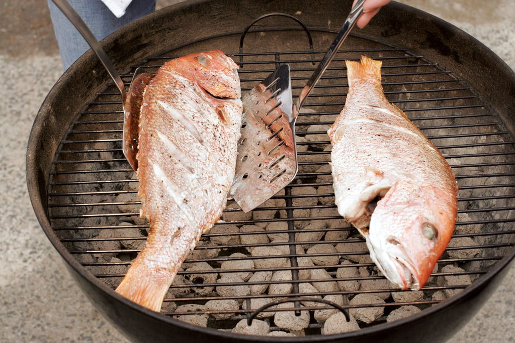 When the fish is ready to be turned, slide one metal spatula under the belly, being careful not to tear the skin. Place another spatula just under the backbone of the fish. Lift up the spatula under the backbone to flip the fish, using the opposite spatula to ease the other side of the fish onto the grill.