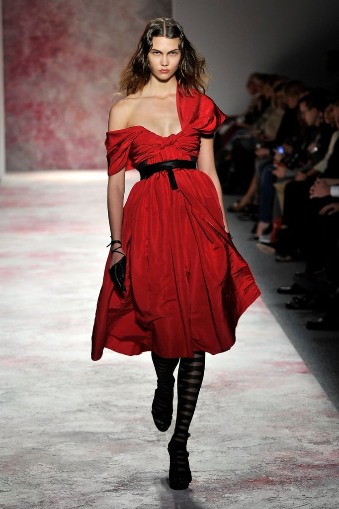 ">> Prabal Gurung had us at look number one — when Karlie Kloss stomped out in a brilliant red dress, sexy in its full party skirt and sleeve nonchalantly slipping off one shoulder. The designer says he was dually inspired by John Singer Sargent's A Parisian Beggar Girl and Miss Havisham from Great Expectations for Fall 2011, but really, it was about a simple challenge: ""Can I do undone? . . . After such a long time of tight, short dresses constantly, I thought that was something so chic."" Gurung returned to his dressier roots after last season's more sportswear-driven stint — there were textures galore (furs, sequins, intricate appliques and the like, which made for some expensive-looking pieces). But that's not to say that the collection was uber feminine; in fact, with its black leather moto gloves and leather lashings around the waist, it forayed into edgier territory than Gurung has tried in the past. Pink hair streaks (which have also been spotted this week on stylist and WSJ contributor Lauren Goodman and the model Charlotte Free) finished off the look, and evidence that the designer's star keeps rising came in both the caliber of model cast (Kloss, who walked Gurung's show for the first time, Constance Jablonski, Jourdan Dunn, Joan Smalls, Liu Wen) and the number of editor-in-chiefs in the front row (including Robbie Myers, Emmanuelle Alt, and Anna Wintour, who was joined by Bee Shaffer)."