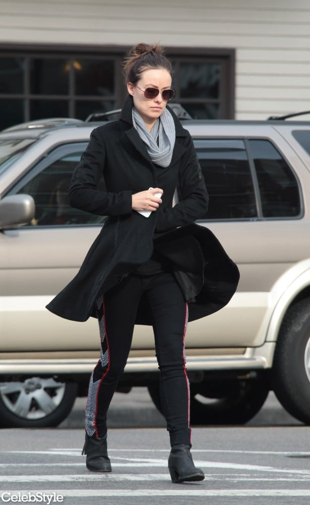 Olivia stepped out in a flared black peacoat, print-paneled Rag & Bone leggings ($286), black ankle boots, classic aviators, and a ribbed scarf.