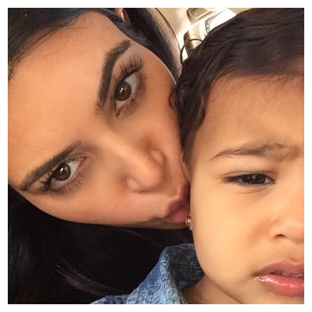 """I don't know if she's annoyed with my million daily kisses or my alien face,"" Kim wrote about this cute picture."