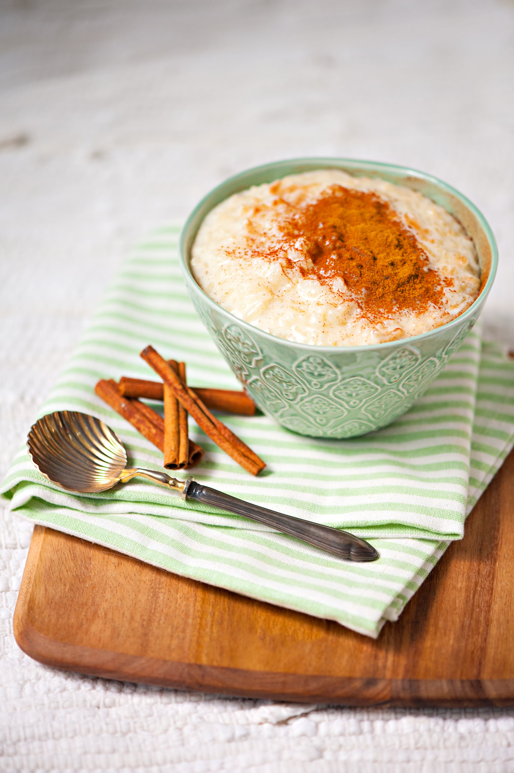 Milk rice pudding in green porcelain bowl with cinnamon powder on top, on a wooden board as background