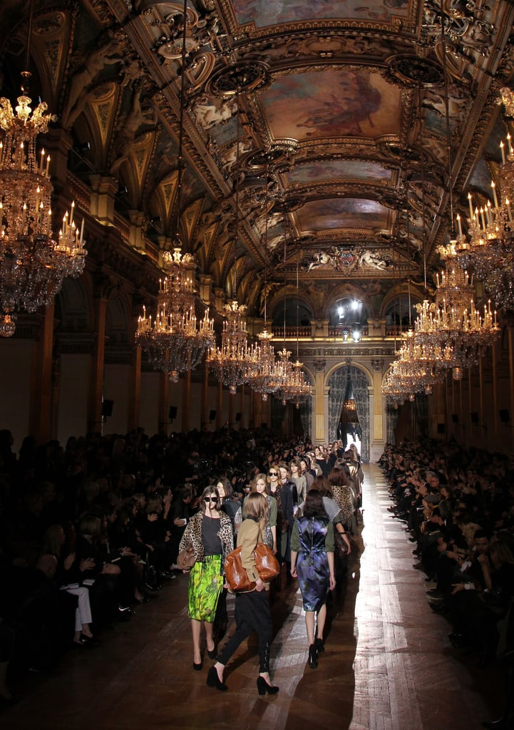 ">> Dries van Noten took fashion show security to a new level today in Paris: everyone's bags had to be scanned, airport-style, before entering the show venue, which just so happened to be the Salle de Fetes (the mayor's party room), in Paris' historic City Hall. Against the setting's gilded, painted ceiling and decadent hanging chandeliers, van Noten sent out an army of military green, leopard print, hand-painted silks, tops cut off and frayed at the shoulders, and hourglass-shaped coats to a Malcolm McLaren-curated soundtrack. ""We started with '50s and '60s couture, the beautiful shapes, and also looked at other garments, menswear, military uniforms and mixed them together in a rebellious way,"" the designer said backstage. ""You get the same elegance, but in a really different way."" Jane Birkin, in jeans and faded Western shirt, and Jared Leto were both front row taking it in."
