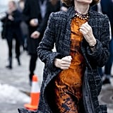 Anna Wintour made a stylish run around the tents in tweed and an abstract-print sheath.
