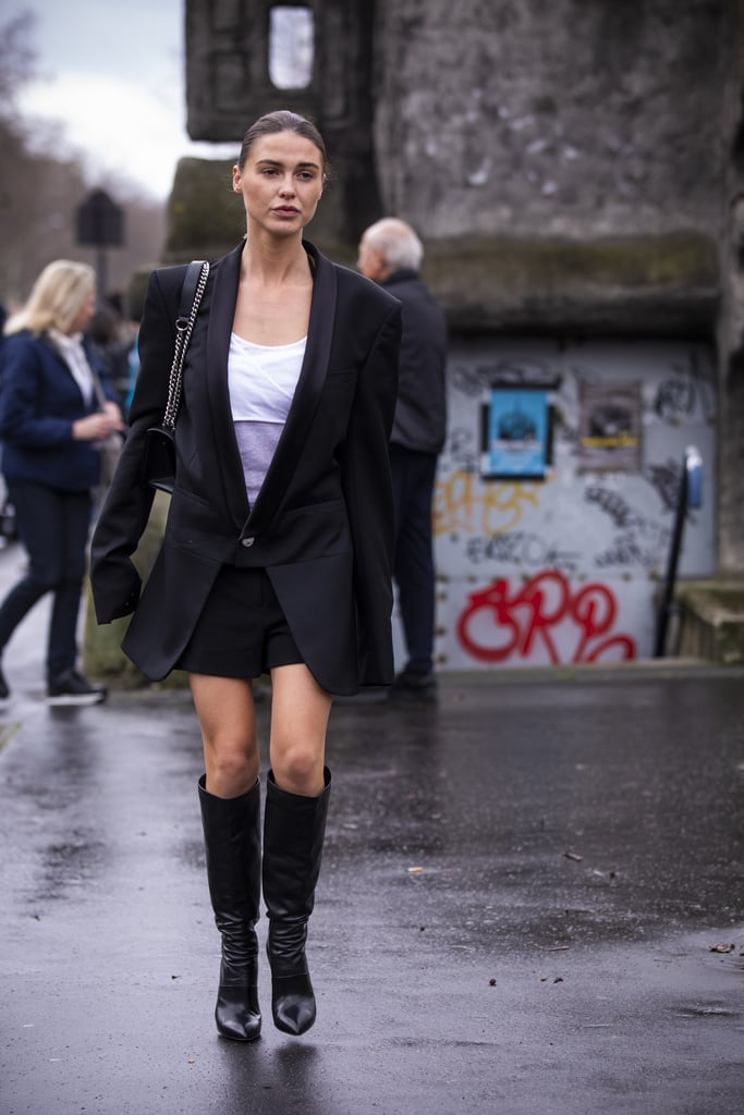 For an adult take on a school uniform, style a white tee with an oversize blazer, matching skirt, and knee-high boots.