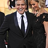 George and Stacy laugh together on the red carpet.