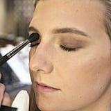 Next, she used a shimmering soft brown eye shadow that she blended all over the eyelid, stopping at the crease.