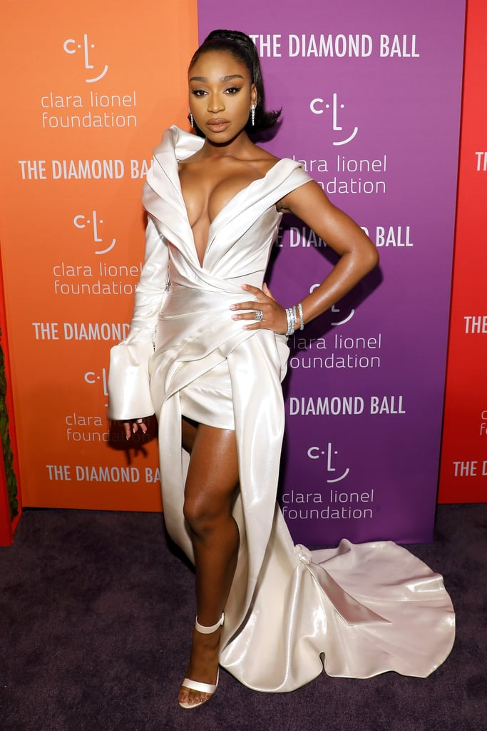 "Normani was one of the lucky attendees of Rihanna's glamorous Diamond Ball on Thursday night, and she definitely lived up to the event's name as she sparkled her way down the red carpet. The ""Motivation"" singer not only stacked up a pair of statement-making wraparound Bulgari diamond cuffs, she also added diamond drop earrings and hoops to her revealing, asymmetric satin gown.      Related:                                                                                                           Normani's Sexy Savage x Fenty Look Is the Ultimate ""Motivation"" to Buy Some Lingerie               Normani's single-sleeve dress is by Australian-based label J'Aton Couture, and was first seen on the runway at Melbourne Fashion Week back in August. The brand is best known for its weddings dresses, so it's no surprise that Normani's look came in bridal white, though this is a look that's definitely more suited to the red carpet than a church service. With a plunging neckline and short skirt topped with a dramatic train, it gave the former Fifth Harmony star the best of both worlds when it comes to length, and allowed her to show off her strappy sandals to full effect. Keep reading to see the stunning look from all angles."