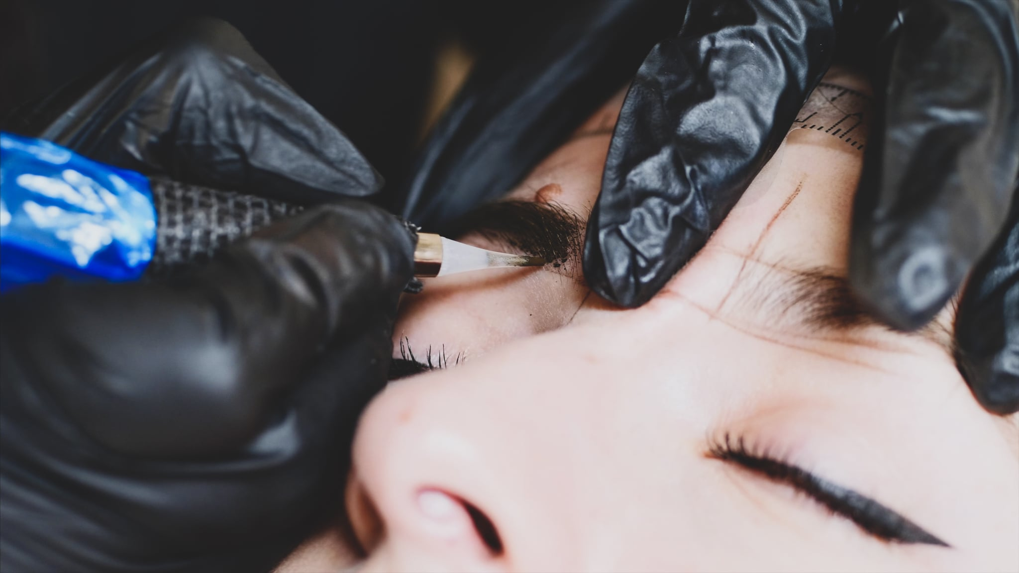 The microblading master in black gloves is filling up the shape of an eyebrow with a pigment holding with one hand woman's head, close-up, camera is above the client.