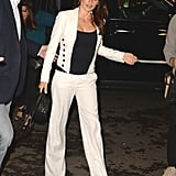 Wearing a wide-leg white pantsuit with a contrasting black tank and pumps.