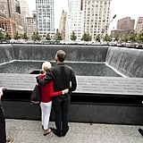 A couple hold each other at the memorial wall on the South Tower reflecting pool of the World Trade Center.