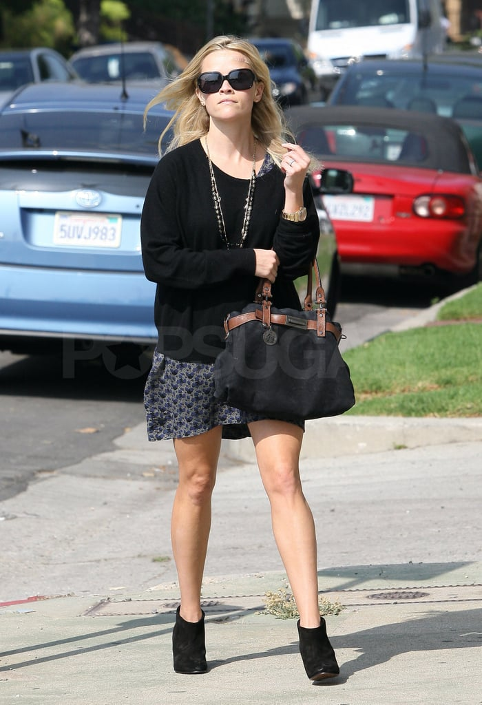 Reese wore cute black booties with her floral skirt.