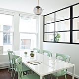 In the conference room, a sleek white and black palette is broken up with wooden chairs painted soft green. Designer Lauren opted for lighting that was less extravagant — but equally as stylish — as the lighting fixtures in the main work area.