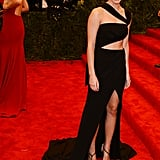 Emma Watson showed serious skin and a smile on her way inside.