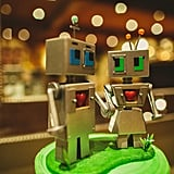 A tiny green cake is topped off with humorous robot wedding toppers.