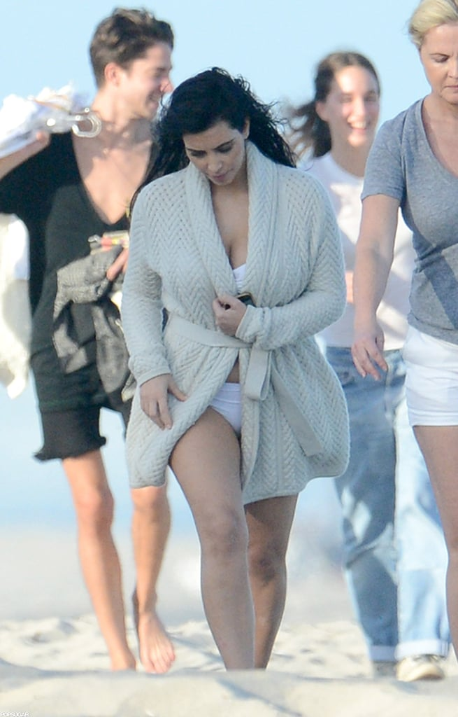 Kim Kardashian wore a white bikini yesterday for a shoot on the beach in Miami. Despite being pregnant with her first child, Kim didn't let any possible chill off the water get in the way of her posing. With the help of a cardigan, Kim's baby bump stayed hidden as she walked from the set back to her hotel.  Kim's in Florida for work and fun. She tweeted about having the chance to dine with her pals Jonathan Cheban and Carla DiBello last night. She and boyfriend Kanye West are equally busy as they kick off 2013. Following their Dec. 31 fun in Atlantic City, Kim was off to host an event last week in Calgary before finding herself back in the Sunshine State.