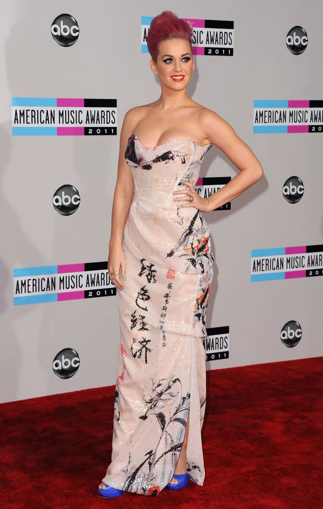 Katy Perry's not afraid of a little drama, as proven by the printed Vivienne Westwood gown, blue heels, and geometrical fascinator the star chose for the 2011 American Music Awards.